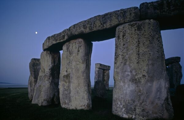 STONEHENGE, Wiltshire. View of part of the Sarsen Circle before sunrise with the moon visible in the background