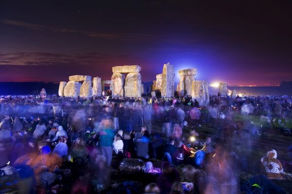 STONEHENGE, Wiltshire. Summer solstice. View of crowds and lit stones. Midsummer before dawn