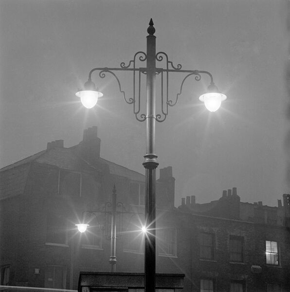 Street lamps, London. Double street lamp with ornate brackets lit at dusk with another identical street lamp behind and the rear of terraced houses in the background, in either Islington or Shoreditch. John Gay. Date range: 1960-1965