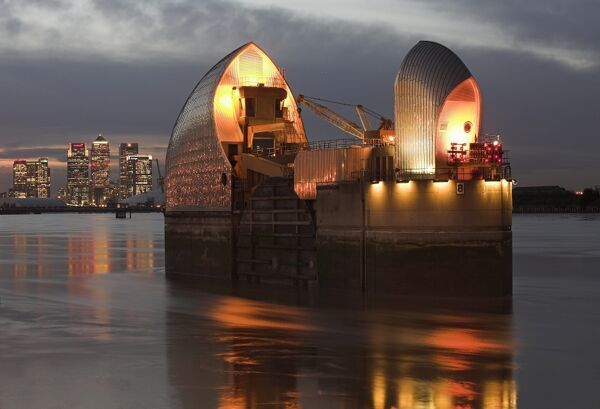 THAMES BARRIER, London. View of one of the tidal / flood control barriers at night showing an illuminated Canary Wharf in the background