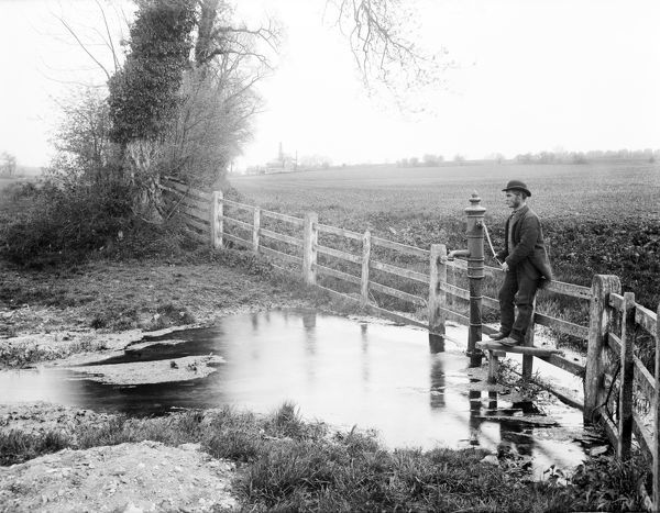 THAMES HEAD, Coates, Gloucestershire. View at the source of the River Thames in the Cotswolds at Thames Head. Showing the fourth spring and man beside the pump. Photographed by Henry Taunt in 1890