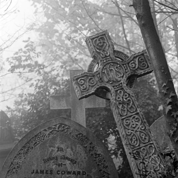 HIGHGATE CEMETERY, London. A leaning Celtic cross beside a gothic headstone dedicated to James Coward in the East Cemetery. Photographed by John Gay. Date range: 1970-1999