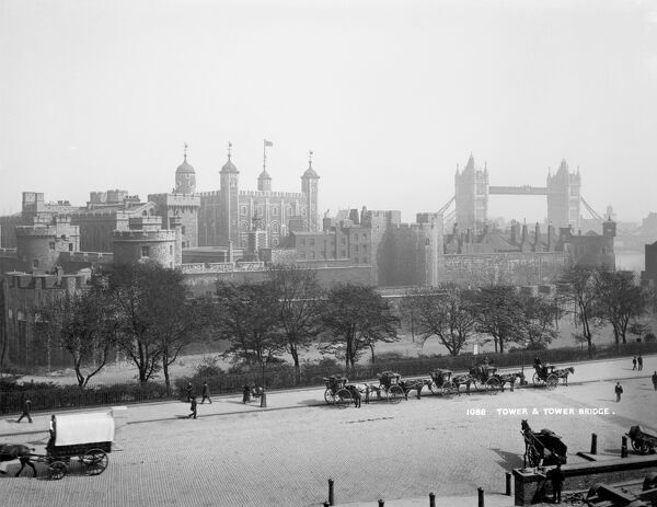 TOWER OF LONDON, Stepney, London. A view across a street and towards the Tower of London to the south-east with Tower Bridge in the background and Hansom Cabs in the foreground waiting for passengers. York and Son. Date range: 1894-1900