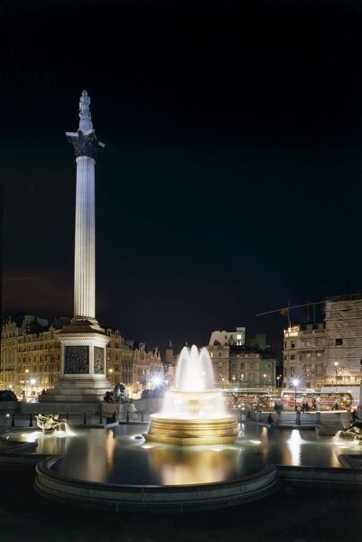 TRAFALGAR SQUARE, London. Night view of the square showing floodlit fountain and Nelson's Column