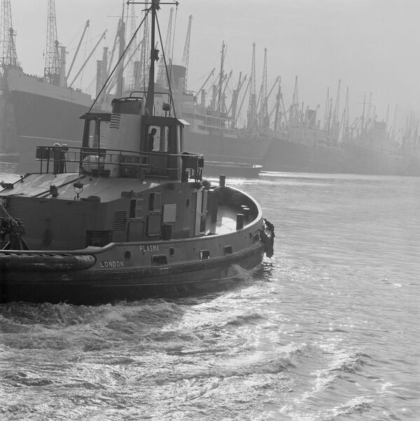 LONDON DOCKS. The tug Plasma in the foreground departing across the water towards a line of moored ships in the London Docks. Photographed by John Gay in July 1965