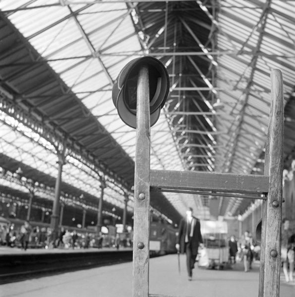 VICTORIA STATION, Westminster, London. Close up view showing a British Rail cap hanging from the wooden handle of a trolley at Victoria railway station. John Gay. Date range: 1960-1972