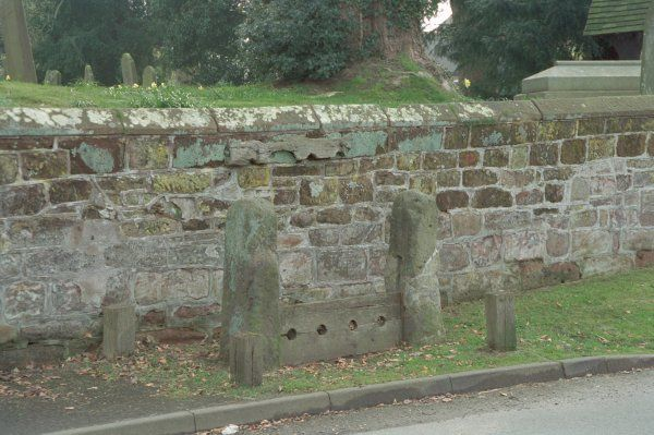 Rectangular stone posts have original slots and 2 late C20 planks with 4 leg holes between. Weston under Redcastle, Shropshire. IoE 428403