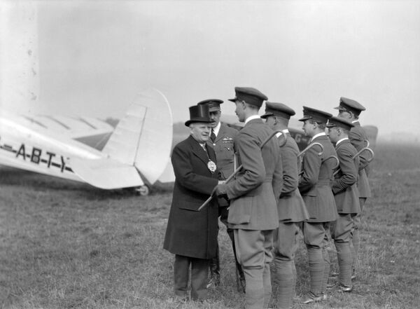 Dignitary and airmen at Heston Aerodrome. The plane in the background is a Spartan Cruiser passenger aircraft operated by Spartan Air Lines Limited on the London-Cowes (Isle of Wight) route between 1933 and 1935. It crashed in the Channel in May 1935