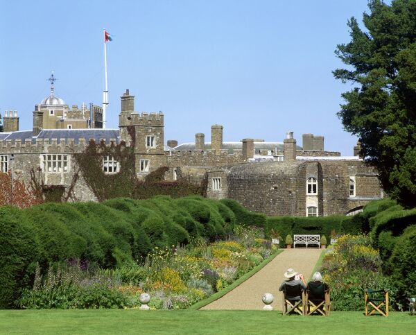 WALMER CASTLE AND GARDENS, Kent. A view of the castle from the Broadwalk with visitors sat on chairs