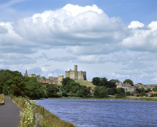 WARKWORTH CASTLE, Northumberland. Distant view of the castle from the South East with the River Coquet in the foreground