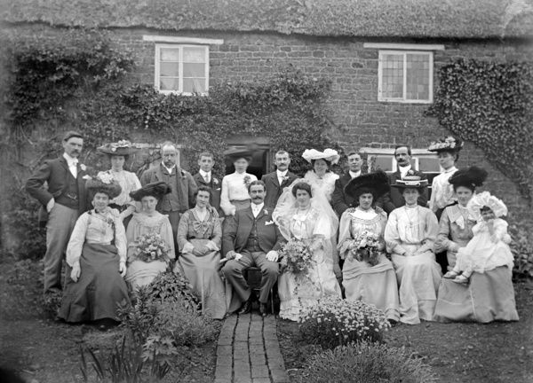 Hellidon, Northamptonshire. General view showing a wedding party posed in front of an unidentified house. Dated sometime between 1896 and 1920 the costume may suggest an Edwardian date. Photographed by Alfred Newton and Son c.1910