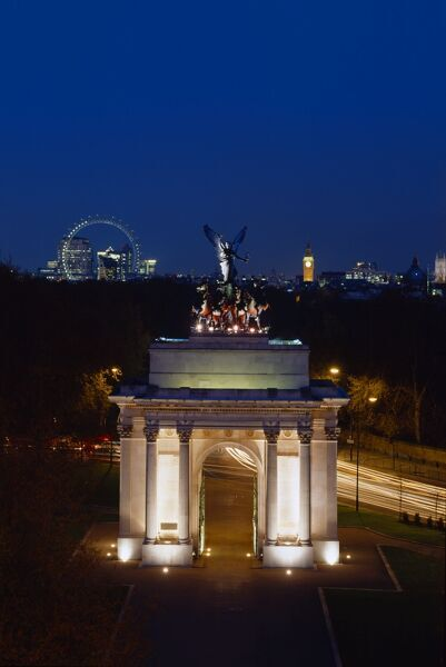 THE WELLINGTON ARCH, Hyde Park Corner, London. A view from the Lanesborough Hotel of the arch floodlit at night with ' Big Ben ' and the London Eye wheel in the background