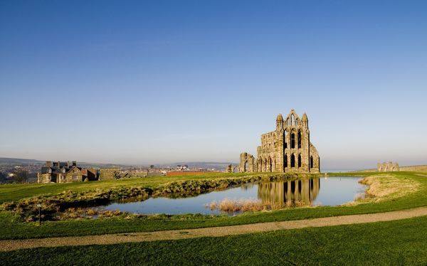WHITBY ABBEY, North Yorkshire. Early morning view of the Abbey across the fishpond