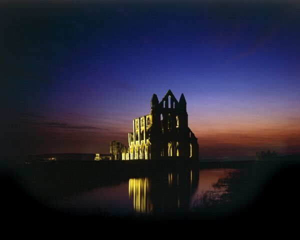 WHITBY ABBEY, North Yorkshire. A floodlit view of the abbey at night with reflection in the water
