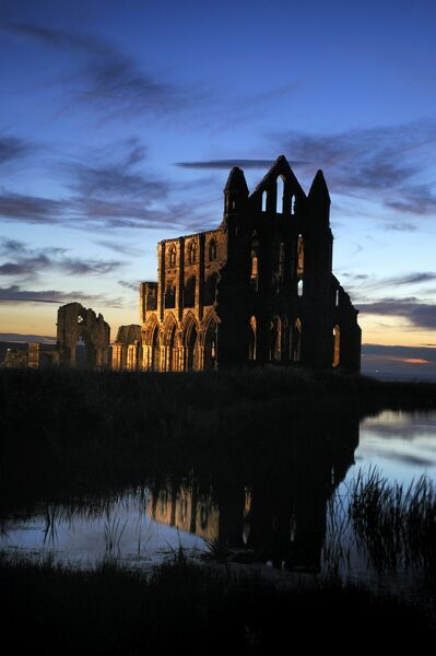 WHITBY ABBEY, North Yorkshire. Floodlit view of the abbey at sunset from across the pond