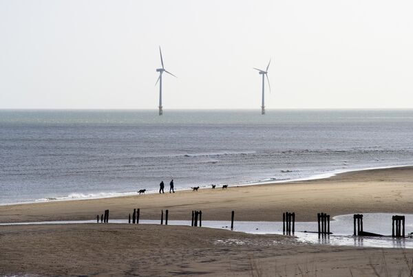 WIND TURBINES, Blyth, Northumberland. View across the beach towards two wind turbines that are part of the Blyth Offshore Wind Farm