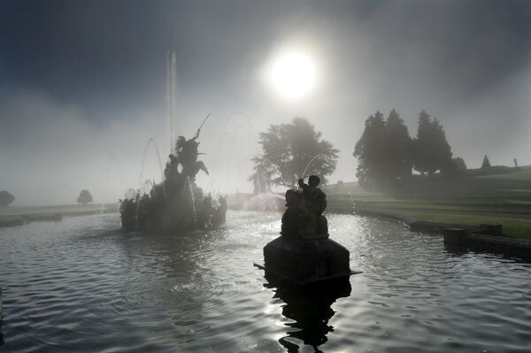 WITLEY COURT AND GARDENS, Worcestershire. The sun shining through a veil of mist produced by the fountain