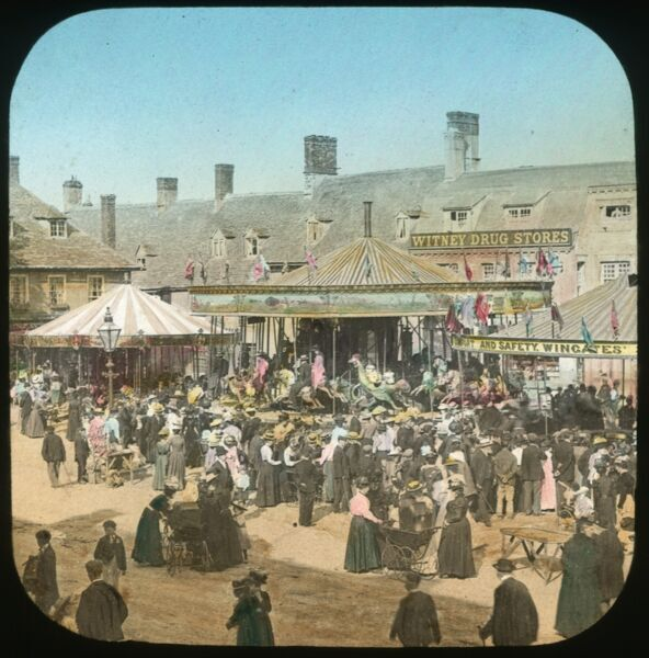 Witney, Oxfordshire. Carousels at Witney Fair, with crowds watching the fun. Hand-tinted lantern slide photographed by Henry Taunt 1890s