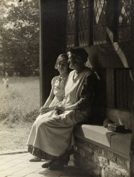 An elderly woman and a young girl seated in a church porch. From an exhibition print by the photographer William Archer Clark, early 20th century