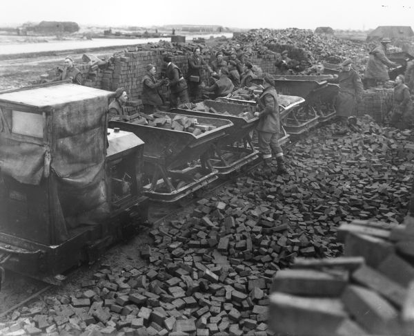 "British troops using a 2' 0"" gauge Ruston & Hornsby diesel locomotive and Hudson tipping wagons while rebuilding an airfield"