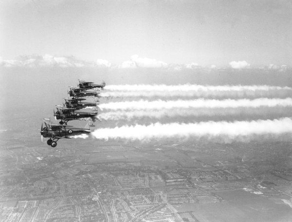 Bristol Bulldog IIA aircraft of 2 Squadron RAF performing smoke aerobatics whilst practising for the Hendon Air Display, 1935