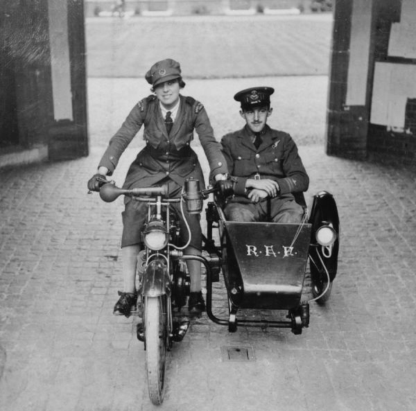 An Airwoman of the Women's Royal Air Force on a motorcycle with an observer officer of the Royal Air Force in the sidecar