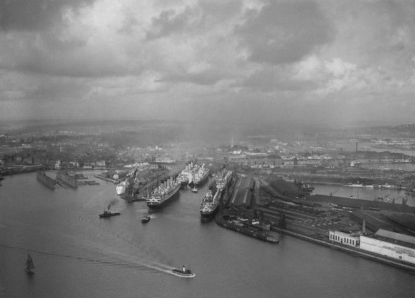 Aerial view of the liner terminal at Southampton with several ships berthed; tugs are assisting one which is about to leave