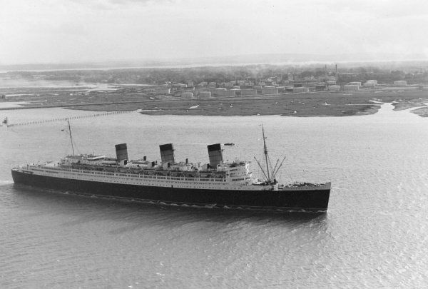 The liner SS Queen Mary passing Fawley oil refinery on her way to Southampton, 1961