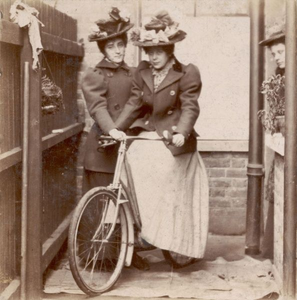 A young lady in 'practical' outdoor dress of tailored skirt & jacket holds a bicycle steady for her friend who sits on it to have her photograph taken. Both wear straw hats