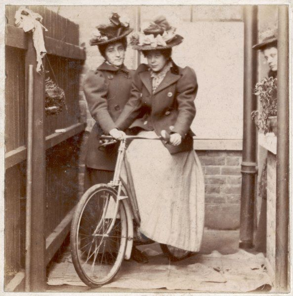 Two young lady cyclists pose with a bicycle at the back of a house. A friend looks on from a doorway. One lady is obviously a novice & requires that the cycle is steadied