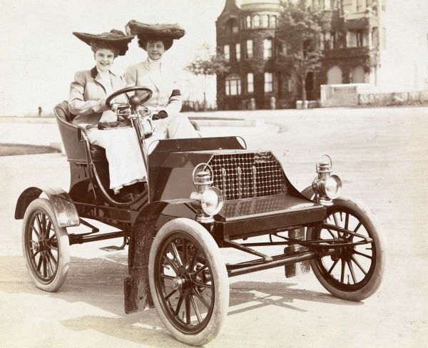 Automobile (Cars). Two women seated in a 1902 Franklin roadster on Riverside Drive; large house visible beyond