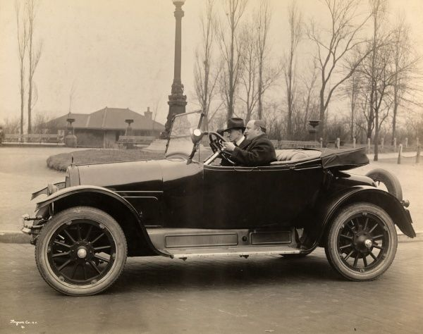 Autos, Old Styles. 1919 Overland Roadster automobile with driver and one passenger parked on a road