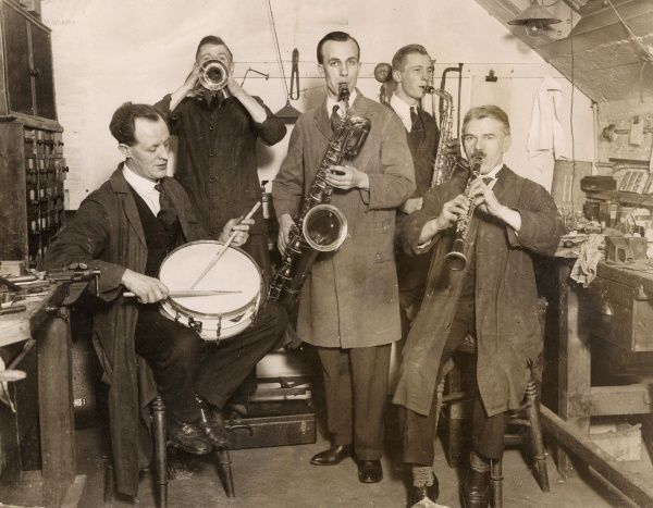 Experienced players in a West End (of London) workshop, who daily repair instruments belonging to famous bandsmen, have formed a band, thoroughly testing all the instruments! Date: 1920s