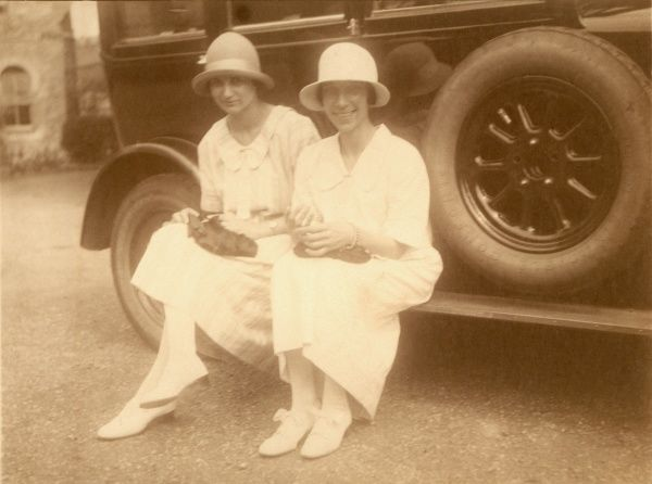 Two ladies in very typical 1920s attire of rounded brimmed hats and long pale dresses sit on the running board of a large tourer