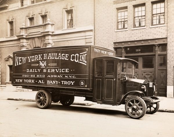 Automobile. A circa 1921 Pierce Arrow moving van parked on the street, buildings visible behind; broadside reads New York Haulage Co. Inc./Daily Service/1780-82 Broadway, N.Y.C./New York