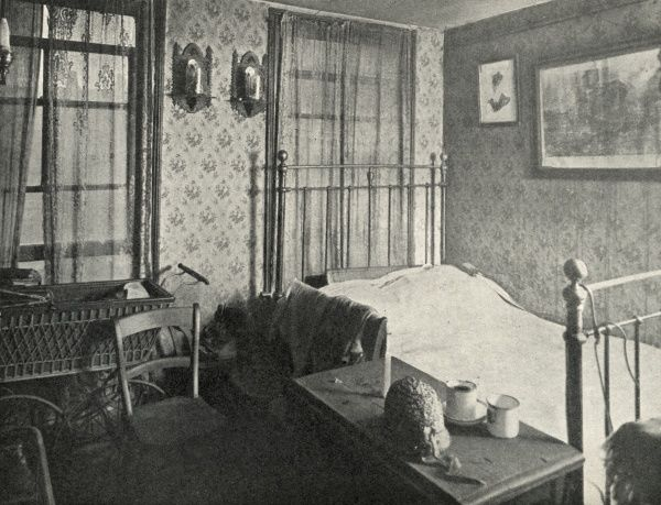 Interior of a cramped one-room dwelling at Bethnal Green. The cramped room contains a double-bed, old pram, and unwashed teacups on a chest of drawers. Date: circa 1936