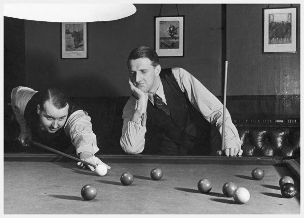 A snooker player prepares to play a shot as his partner looks on. Their smart attire reflects the gentlemanly traditions of the game