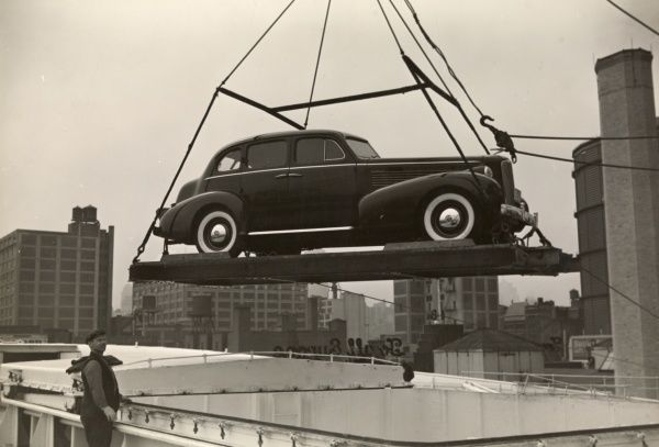 Automobile (Cars). 1937 LaSalle automobile being loaded onto a French Line ship with a crane; skyline visible beyond