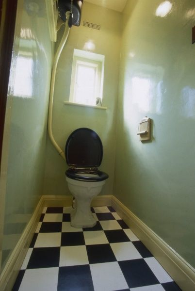 A typical 1940s lavatory, with green walls and black and white floor tiles, separated from the bathroom
