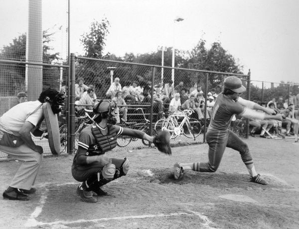 A batter swings at the ball during a game of baseball, watched by a small crowd. Date: 1950s