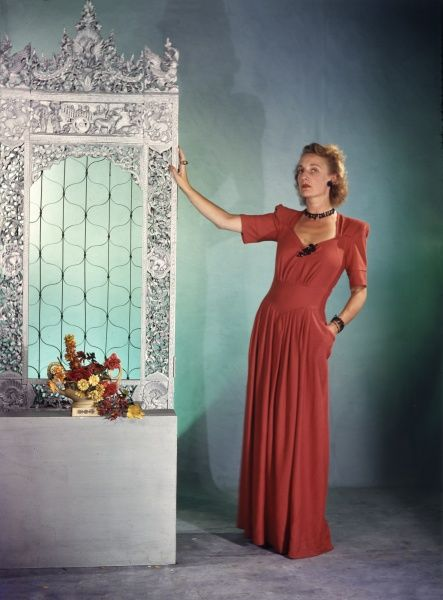 A bored looking model poses wearing a long coral coloured evening gown, against a rather bizarre studio prop