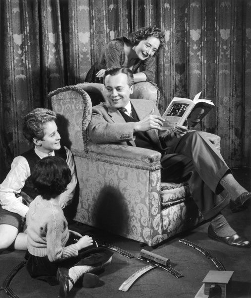 A classic nuclear family in their living room, the children playing with a train set, the Father reading his book or magazine in a comfy chair and his wife also having a look at the publication over his shoulder. Photograph by Heinz Zinram