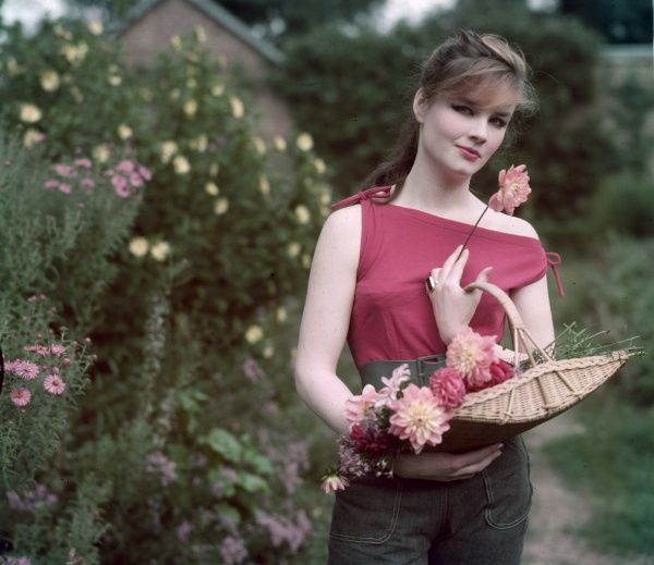 Young woman in denim trousers & hot pink, sleeveless sun top carries a shallow flower basket full to the brim with freshly picked blooms
