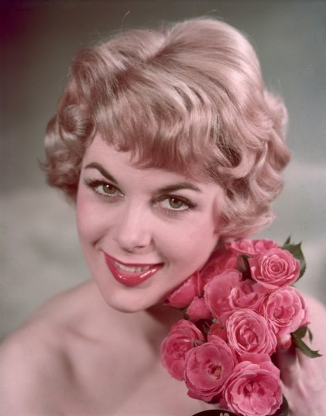 A blonde model with typical short, set fifties hairstyle and glossy pink lipstick poses with a bunch of pink roses