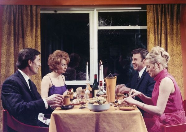 A 1960s dinner party. Two couples enjoy a jolly (if very formal!) evening meal with distinctive sixties period crockery, costume and interior decor. Photograph by Heinz Zinram