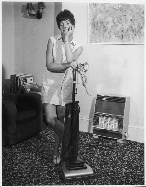 A British housewife poses with Hoover and rag in the centre of her sitting room