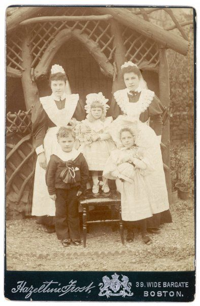 Two nursemaids pose with their three charges outside a summerhouse