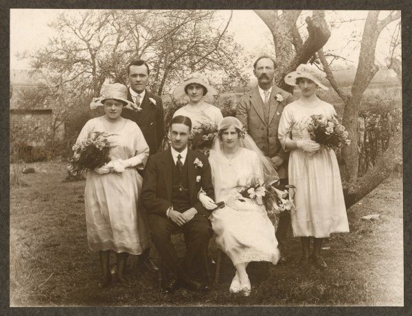 A small wedding group consisting of the bride and groom; three bridesmaids and two other men, one of whom looks like the father of the bride. Photographed outside