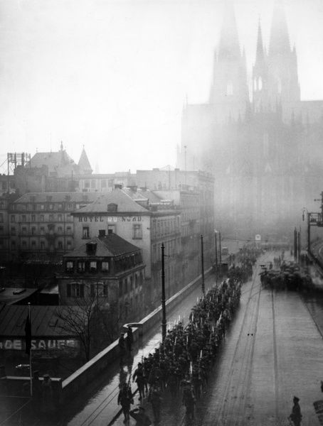 The British 29th Division entering Cologne, Germany, by the Hohenzollern Bridge during the First World War, with General Plumer taking the salute. A misty cathedral can be seen in the background