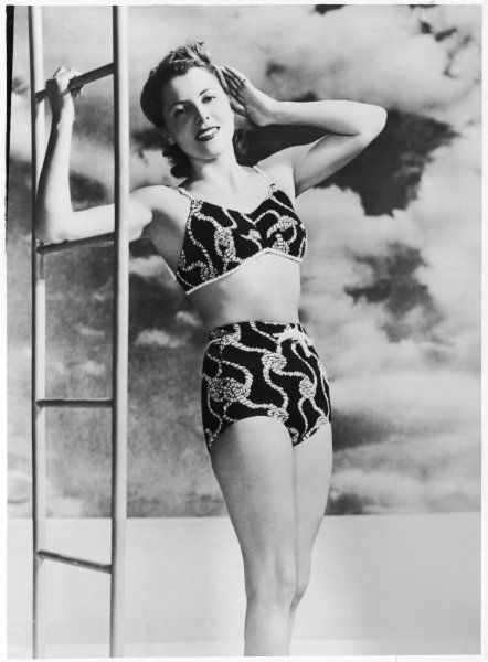 A young lady about to ascend the ladder to the diving board wears a striking two-piece swim-suit in black & white, with a design of knotted ropes
